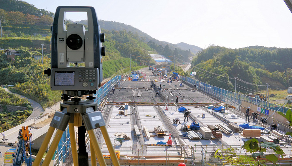 Automatic tracking-type total station installed at the top of a hill overlooking the entire bridge surface; the casting processes of fresh concrete were surveyed and recorded automatically.
